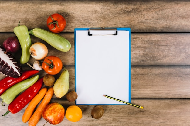 Fruits and vegetables near clipboard