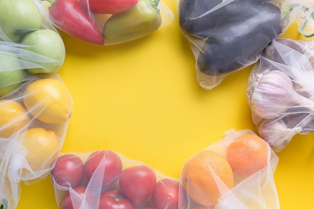 Fruits and vegetables in reusable bags frame background