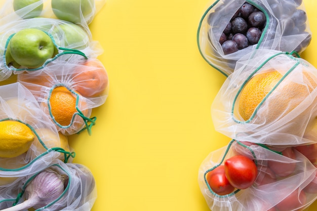 Fruits and vegetables in reusable eco-friendly mesh bags on bright yellow