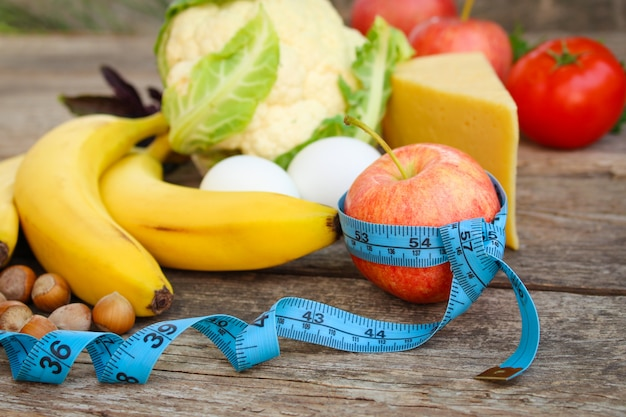 Fruits and vegetables, tape measure on old wood concept of proper nutrition.