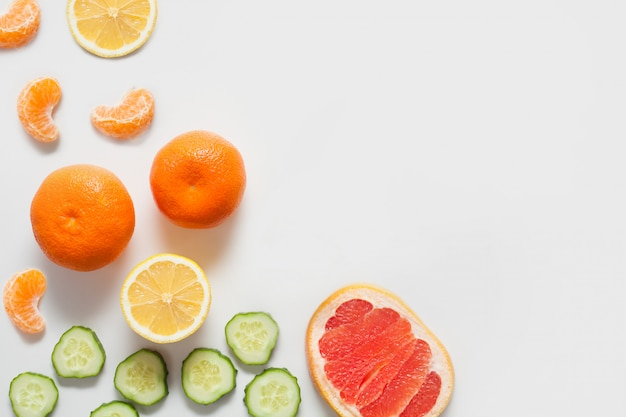 Fruits and vegetables on a white wall, including citrus lemon and tangerines, grapefruit and fresh sliced cucumber. concept vitamins, healthy food, walls for grocery stores.