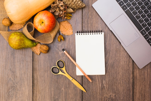 Fruits and vegetables with notepad on table