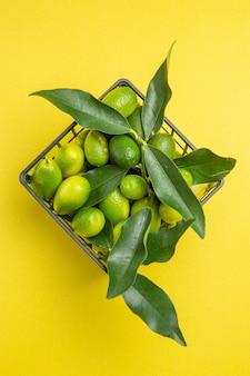 葉のある果物テーブルの上の灰色のバスケットに葉のある緑の果物