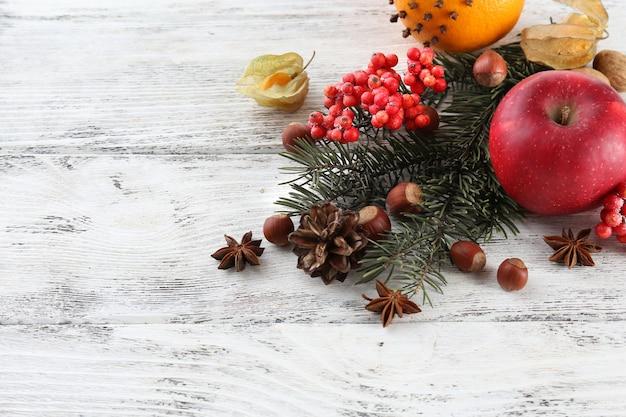 色の木製の背景にスパイスナナカマドとクリスマス松の小枝と果物