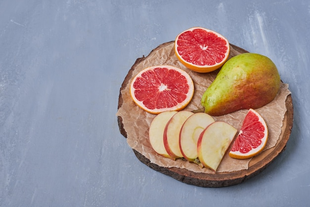 Fruits on a wooden board on blue