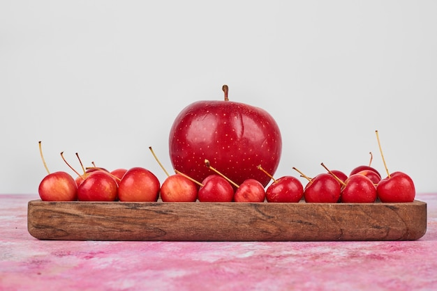 Fruits on wooden board on pink.