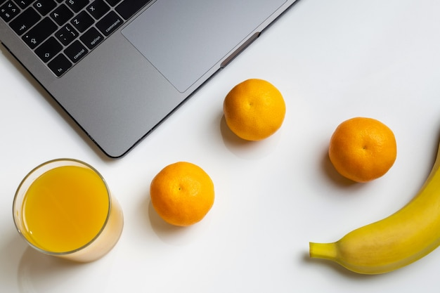Fruits on workplace. laptop, banana, mandarins and orange juice on white desk.