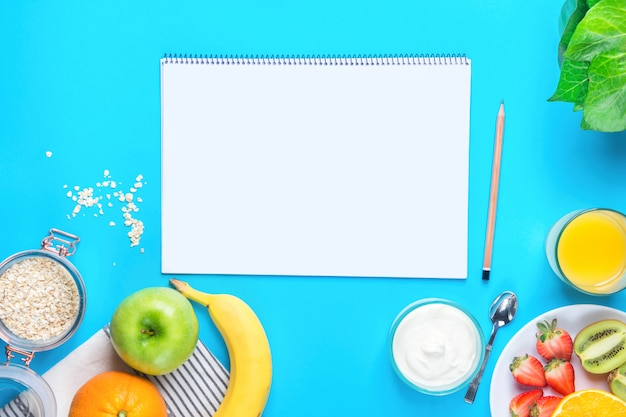 Fruits, yoghourt, oats and blank notepad on blue tabletop background.
