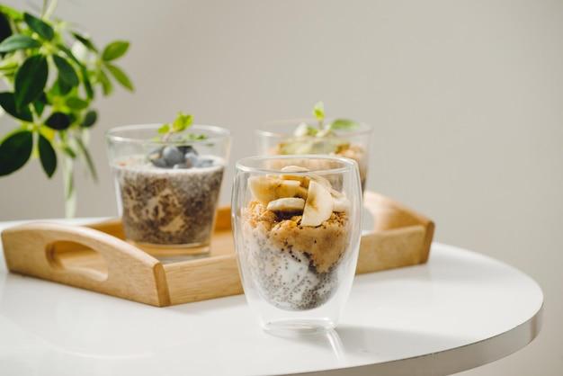 木製のテーブルで健康的な朝食のためのグラノーラとチアシードとフルーツヨーグルトパフェ