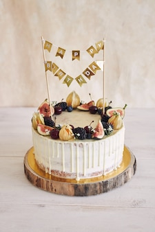 A fruity birthday cake with birthday topper, fruits on top and white drip on beige background