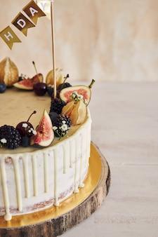 Una torta di compleanno fruttata con topper di compleanno, frutta in cima e gocciolamento bianco su beige