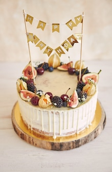A fruity birthday cake with birthday topper, fruits on top and white drip