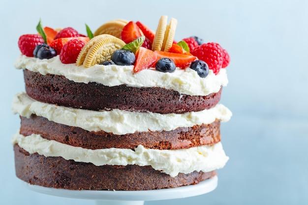 明るい背景のスタンダーに新鮮な果物とクリームとフルーティーなケーキ。