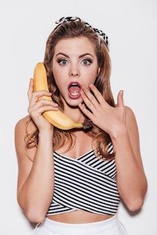Фруктовые сплетни. красивая молодая женщина держит банан как телефон и прикрывает рот рукой, стоя на белом фоне