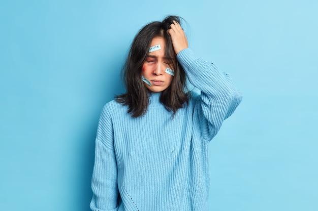 虐待された家庭内暴力の犠牲者である欲求不満の虐待されたブルネットのアサイン女性は、カジュアルなセーターを着た顔に打撲傷を負っています