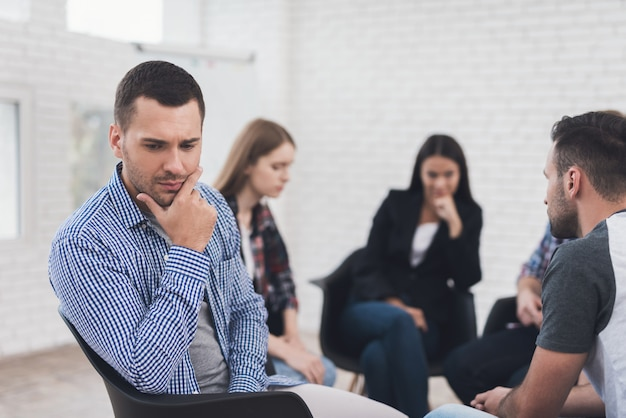 Frustrated adult man is sitting in group therapy session.