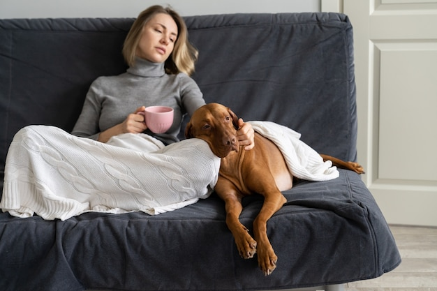 Frustrated adult woman avoid social contacts at home with dog after friend betrayal lover breakup