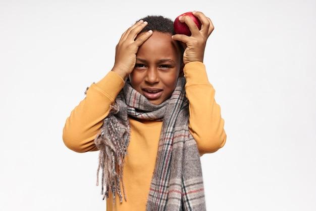 Расстроенный афроамериканский ребенок в шарфе, страдающий от мигрени, держит руки на голове и хмурится.