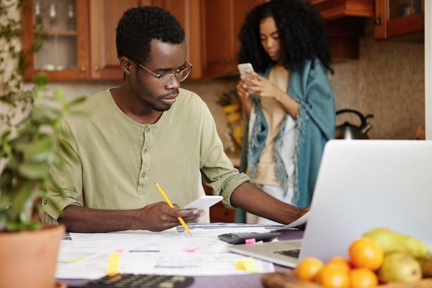 Разочарованный африканский муж в очках держит сотовый телефон и карандаш, управляет семейными расходами и оплачивает домашние счета онлайн