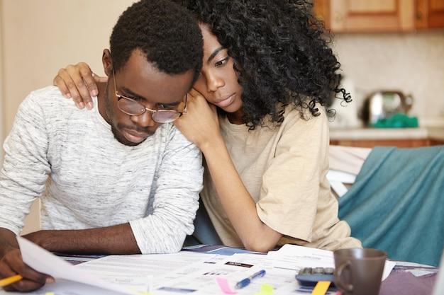 台所のテーブルで事務処理を行う眼鏡を身に着けている欲求不満のアフリカ人