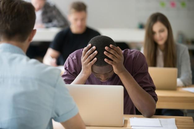 Разочарованный африканский офисный работник с проблемой, держа голову в руках