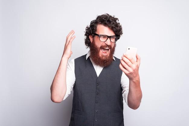 Разочарованный и сердитый человек смотрит на смартфон и кричит, плохие новости