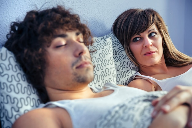좌절하고 화난 여자가 침대에서 자고 있는 젊은 남자를 바라보고 있습니다. 부부 관계와 문제 개념입니다.