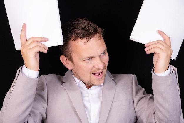 그의 손에 서류와 함께 그의 얼굴에 화가 감정과 좌절과 짜증이 사업가. 비즈니스 개념.