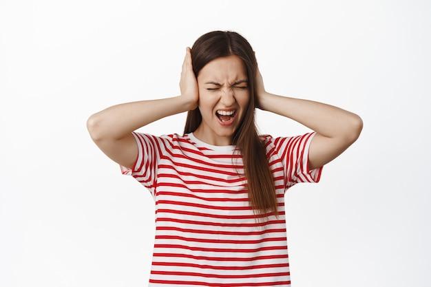 欲求不満でイライラする若い女性が否定的に叫び、聞きたがらず、うるさい大きな音にうんざりし、耳を手で覆い、叫び、白い壁の上に立っている