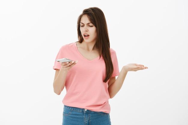 Разочарованная и обеспокоенная брюнетка женщина позирует в студии со своим телефоном