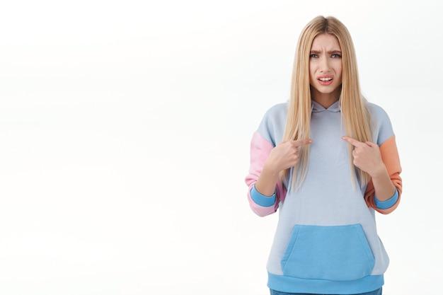 Расстроенная и сбитая с толку очаровательная блондинка со светлыми волосами, выглядящая обиженной или обвиненной