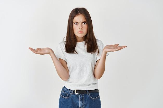 欲求不満で混乱しているブルネットのガールフレンドは、質問をし、失望を表明し、手を横に広げて肩をすくめ、優柔不断で躊躇している白い壁を感じます。