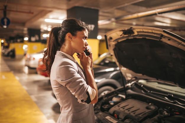 좌절하고 괴로워하는 여성은 지하 차고의 공공 장소에서 자동차 고장이 있습니다.