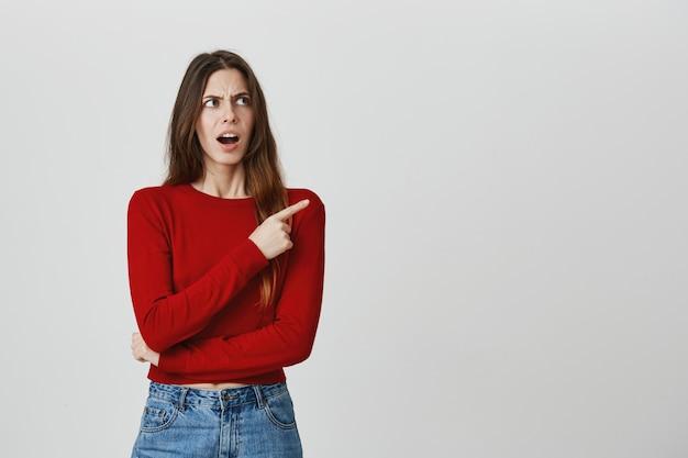 Разочарованный и шокированный, нахмурившись злой женщины, указывая пальцем в верхнем правом углу