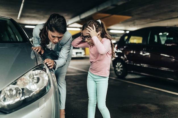 좌절하고 겁에 질린 엄마와 딸이 긁힌 차를 보고 있습니다.