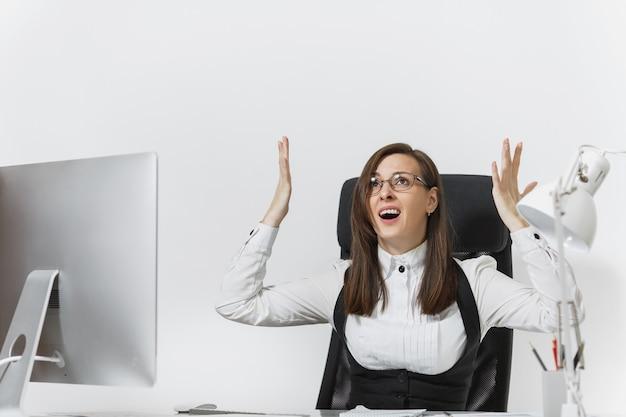 欲求不満の怒っているビジネスウーマンが机に座って、軽いオフィスで書類を持ってコンピューターで働いて、宣誓と叫び、手を上げて、広告用のスペースをコピーします。