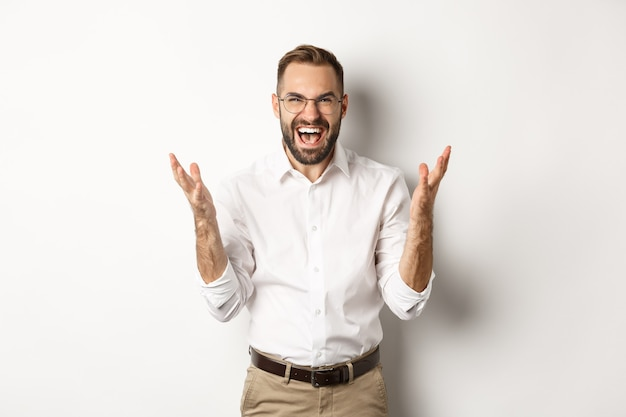 Frustrated and angry man screaming in rage, shaking hands furious, standing over white background. copy space