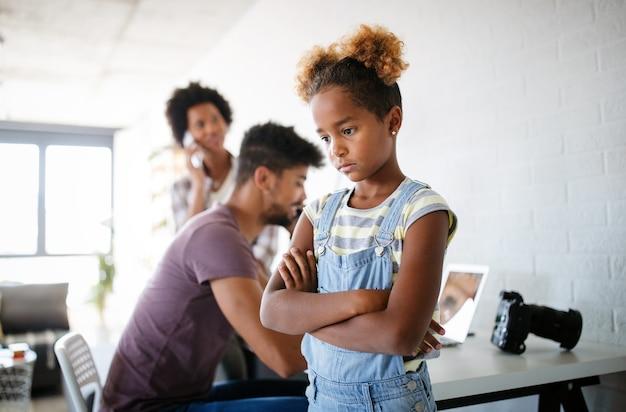 忙しい働く親からの注意を探している欲求不満の怒っている悲しい子供