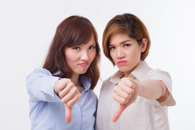 Frustrated, angry women giving rejecting thumb down