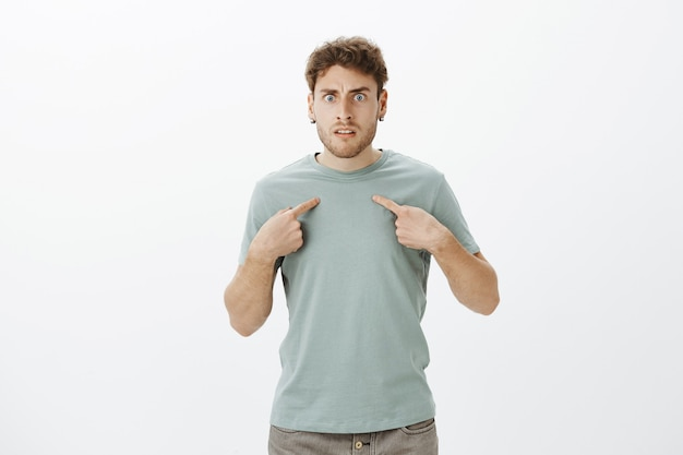 Frustrated angry young man with bristle in t-shirt and earrings, pointing at himself and frowning, being insulted or offended by friend