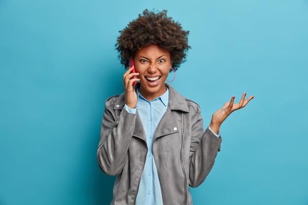 좌절 된 성가신 어두운 피부의 곱슬 머리 여자가 손을 들고, 전화 통화를하고, 세련된 옷을 입고, 적극적으로 몸짓을하고,