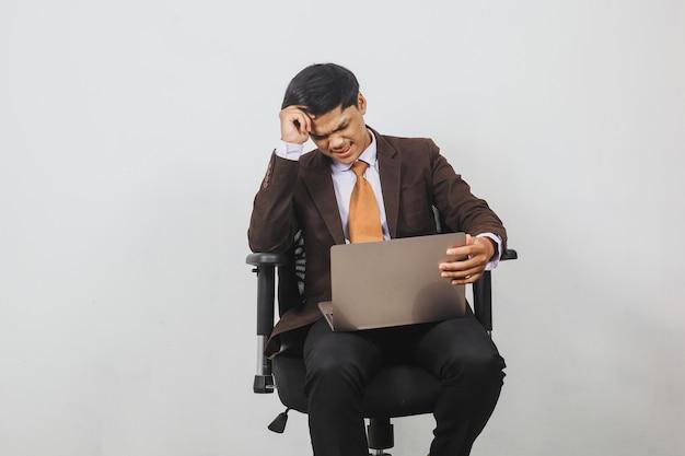 Разочарованный азиатский бизнесмен в пиджаке и галстуке сидит, глядя на ноутбук
