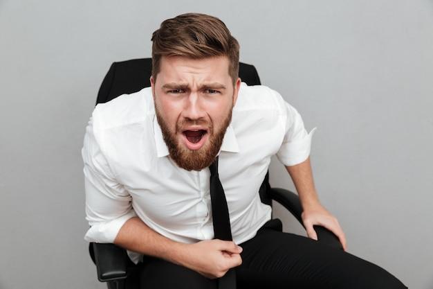Разочарованный бородатый бизнесмен сидит в кресле и смотрит на