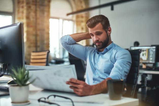 現代のオフィスに座っている間青写真を見ているフォーマルな服装で欲求不満のひげを生やしたエンジニア