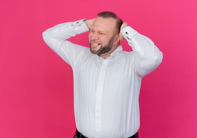 분홍색 벽 위에 서있는 그의 머리를 만지고 흰 셔츠를 입고 좌절 된 수염 난된 남자