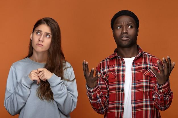 Разочарованный темнокожий темнокожий парень в красной клетчатой рубашке, пожимающий плечами и хмурясь, держась за руки перед собой, не понимает своей несчастной расстроенной белой подруги, у которой месячные