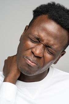 目を閉じて首に手を握って欲求不満の黒人男性が痛みに苦しんでいます