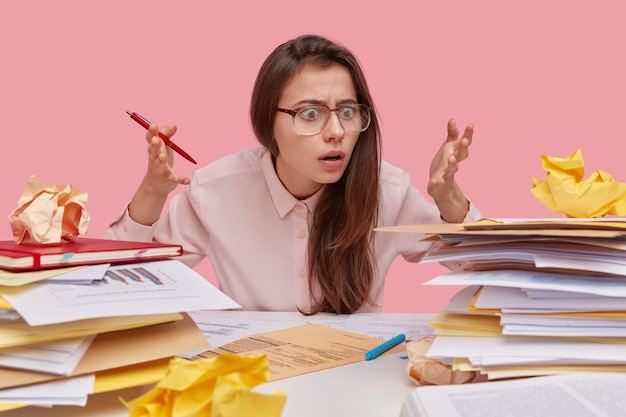 Frustrated brunette lady raises hands with bewilderment and shock, stares at heap of papers, doesnt know from what to start working