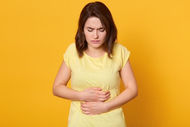Разочарованная брюнетка, держащая руки за живот, чувствует боль при менструации или болезни, носит повседневную футболку, сидит дома