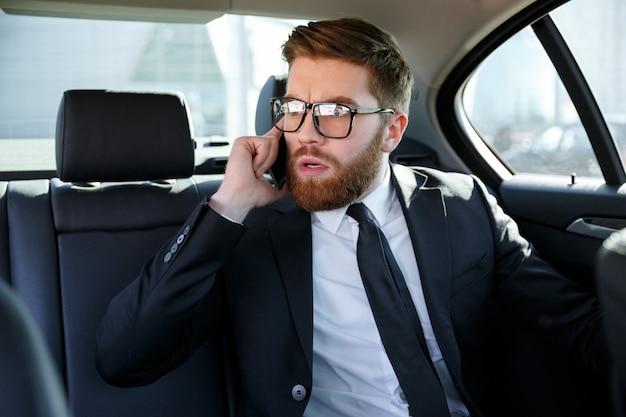 Frustrated business man in eyeglasses talking on mobile phone
